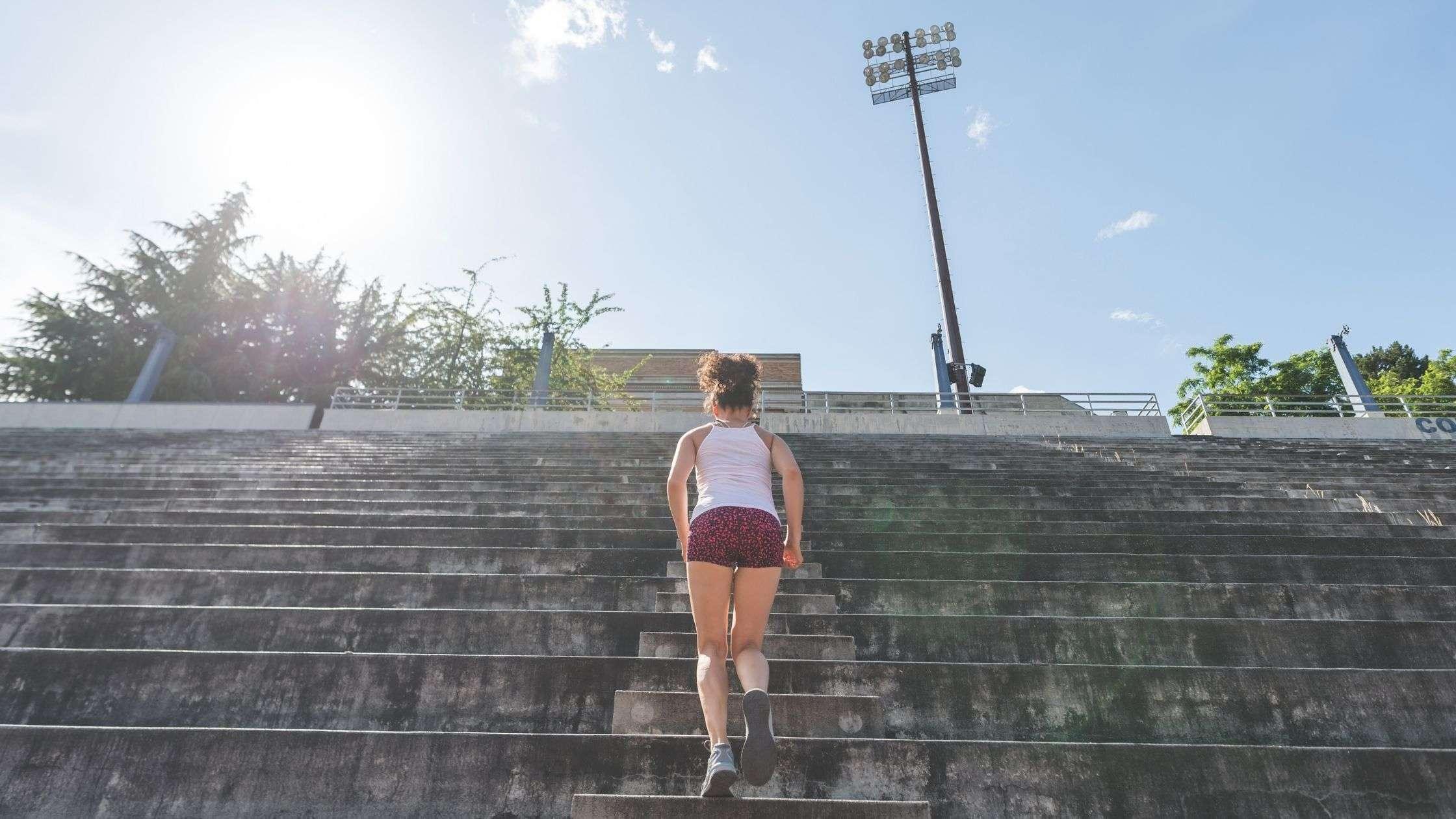 female student athlete running stadium stairs